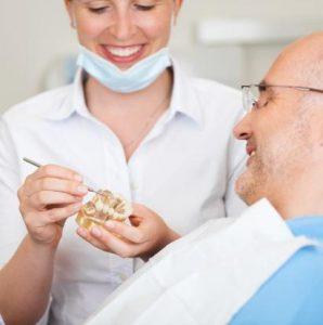 Zahnärztin demonstriert Patient Eingriff an Modell
