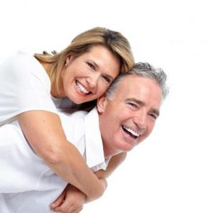 Mann trägt Frau lachend Huckepack