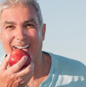 Mann beisst herzhaft in Apfel