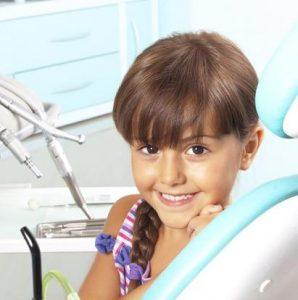 Kind sitzt lächelnd auf dem Untersuchungsstuhl