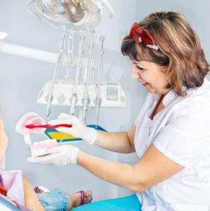 Assistentin zeigt Kind wie man Zähne putzt