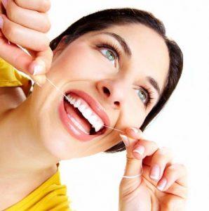 Frau benutzt Zahnseide